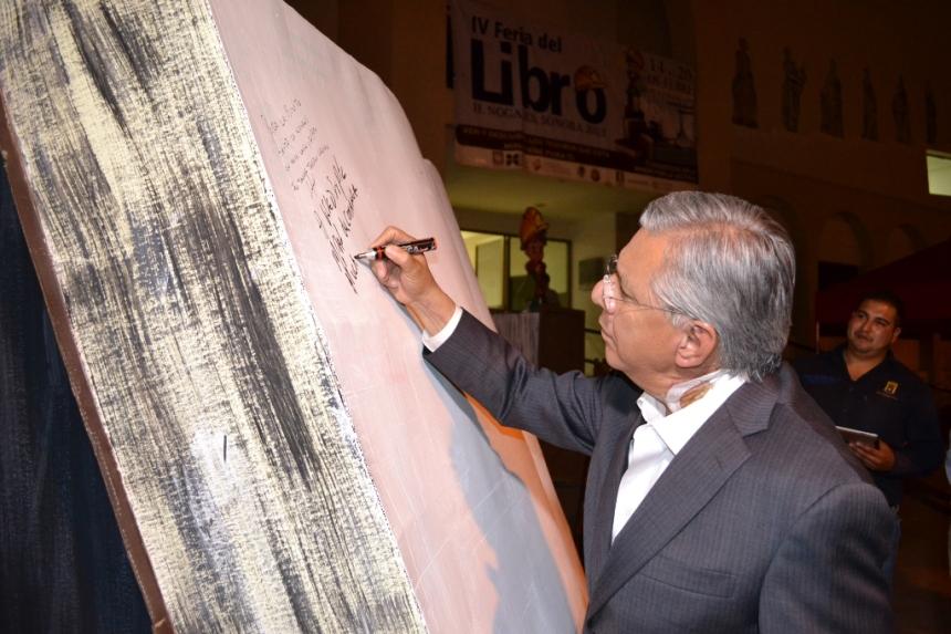 El alcalde Ramón Guzmán firma el libro conmemorativo al evento.