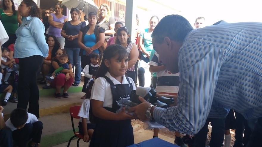 La niña Airam del Jardín de Niños Rodolfo Monroy Rivera recibe su uniforme escolar gratituo de manos del Procurador